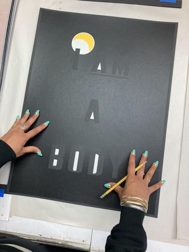Baseera Khan signing <em>I AM A BODY</em>, 2020 edition. Courtesy of the artist and EFA Robert Blackburn Printmaking Workshop, New York.